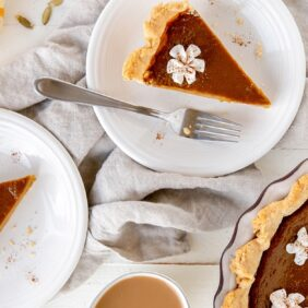 slices of pumpkin pie on round white plates with forks