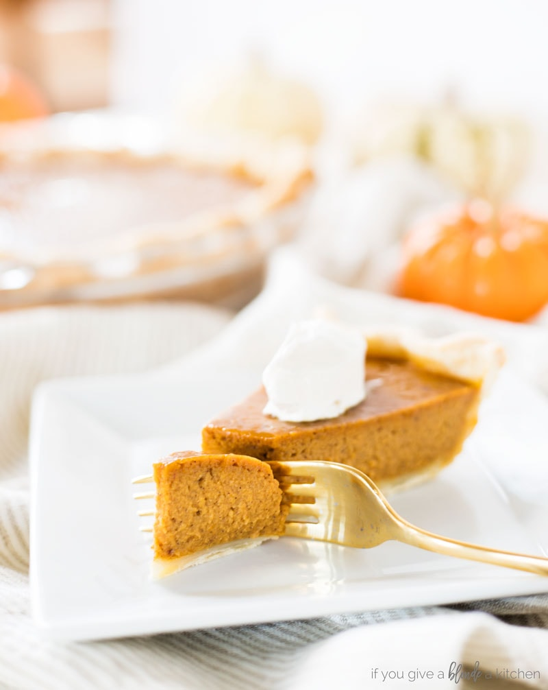 Homemade pumpkin pie recipe with gold fork taking bite of pie