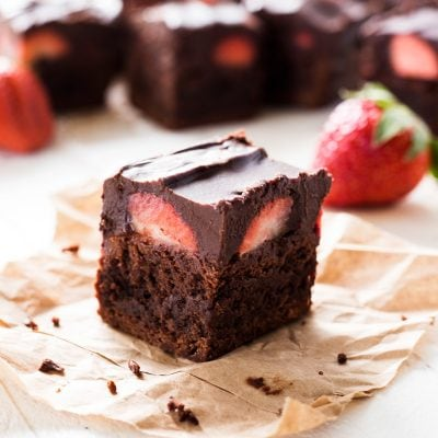 chocolate covered strawberry brownies on parchment paper with strawberries in the background and layer of chocolate ganache on top of fudgy brownie