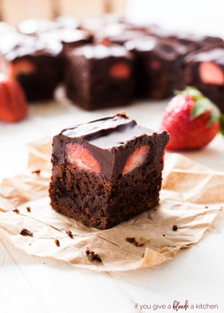 chocolate covered strawberry brownie on parchment paper with strawberries