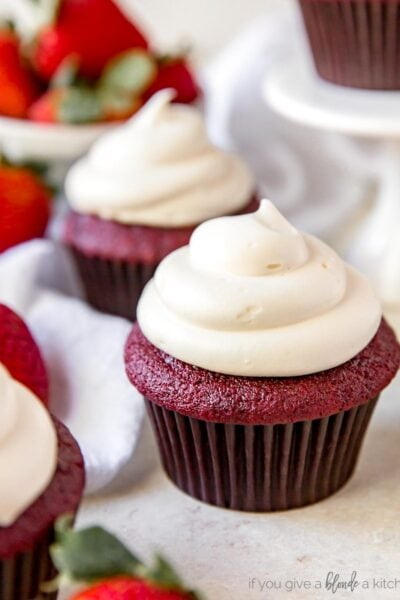 red velvet cupcake with cream cheese frosting near fresh strawberries