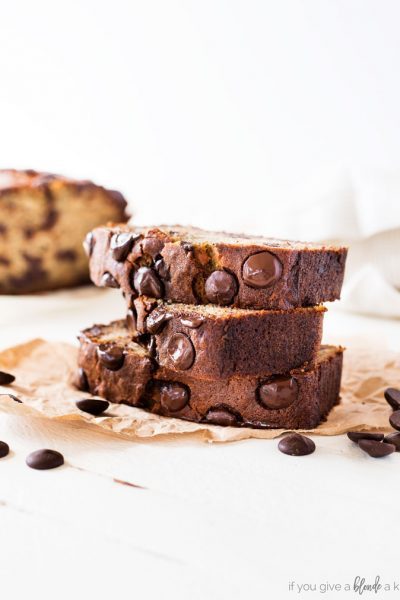 Chocolate chip banana bread recipe slice with chocolate chips on parchment paper, white background
