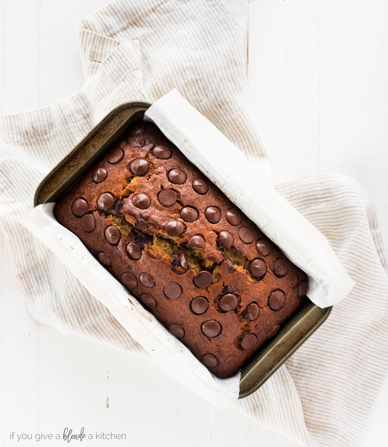 Chocolate chip banana bread recipe bread in loaf pan with parchment paper and thin striped kitchen towel on white background