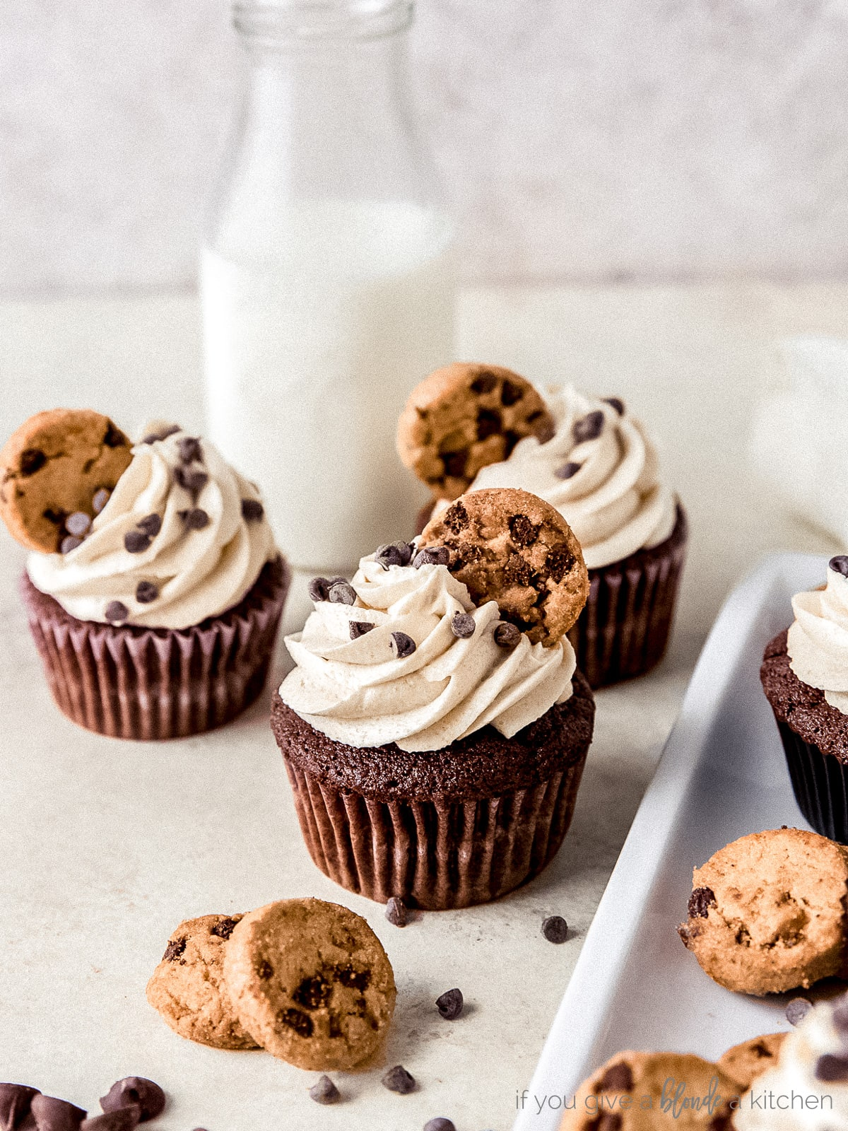 three chocolate chip cookie dough frosting cupcakes in front of tall bottle of milk