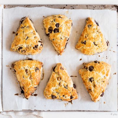 Ina Garten's chocolate pecan scones on parchment paper and baking sheet. Golden, shiny scones with chocolate chips and chopped pecans