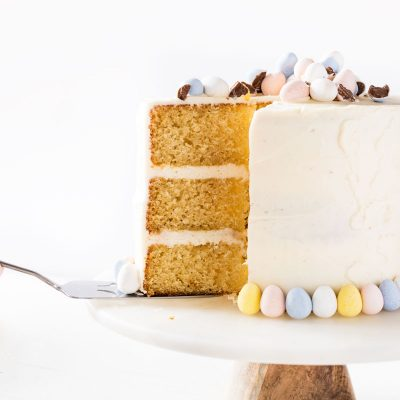 Mini cadbury egg cake. Triple layer vanilla cake with vanilla frosting. Slice of cake removed from cake on marble cake stand with white back ground. Pastel Easter candies decorating the cake