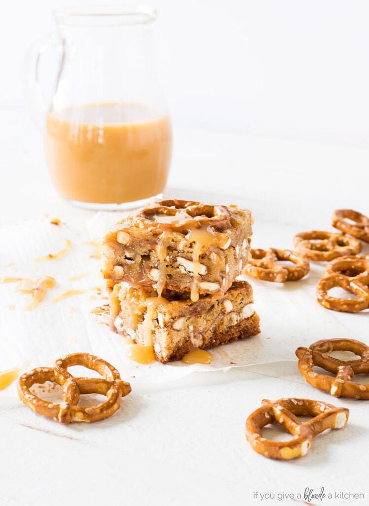 two caramel pretzel blondies stacked on top of each other. pretzel twists next to blondies