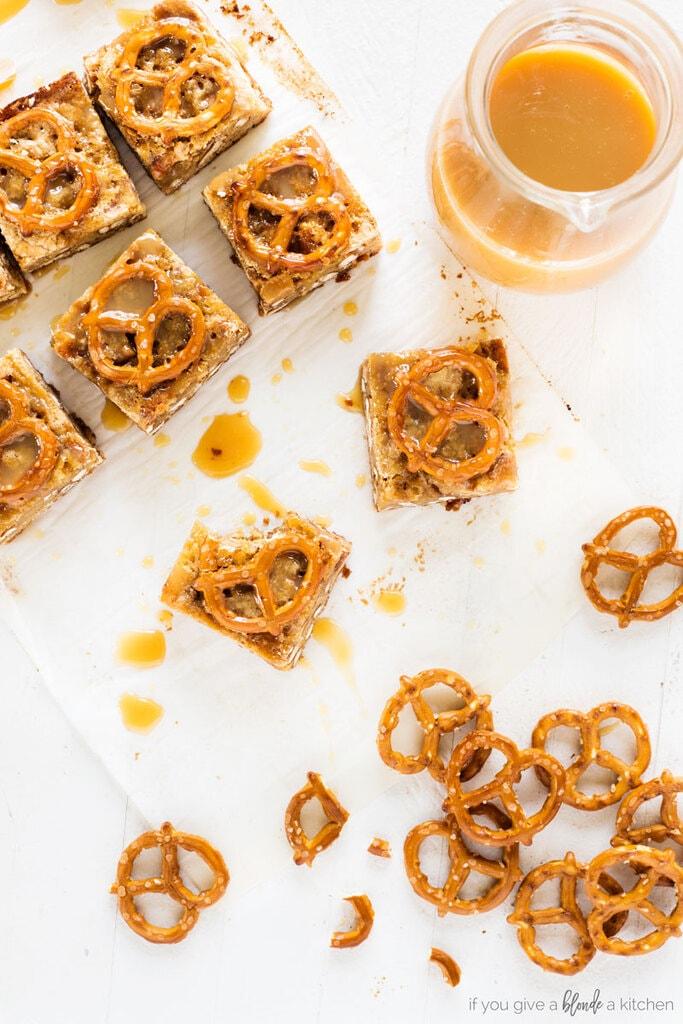 salted caramel pretzel blondies cut into squares. Mini pretzel twists and caramel sauce in pitcher
