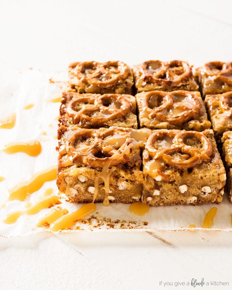salted caramel pretzel blondies. Side view of blondies with pretzel bits and caramel drizzle