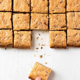 Pecan coconut blondies cut into squares with hand taking one from the symmetrical bars