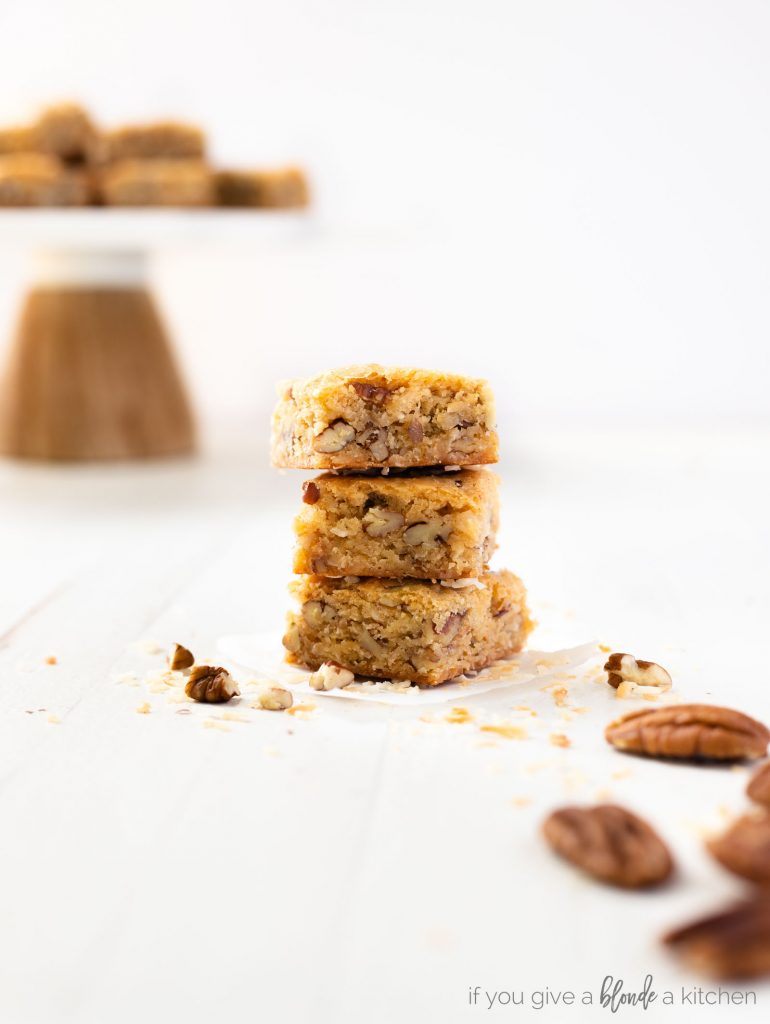 pecan coconut blondies stacked on top of each other showing center of the dessert bars.