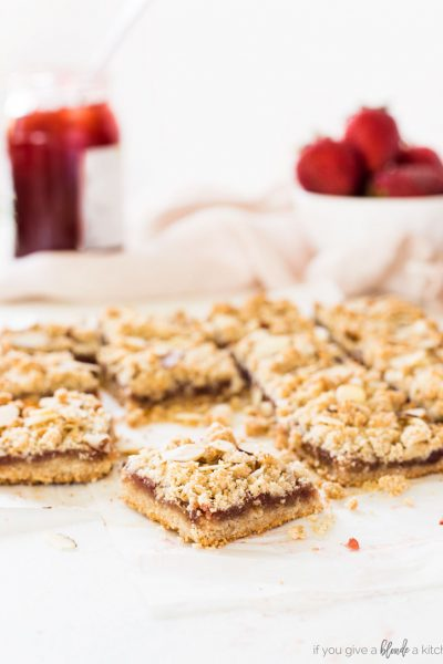 strawberry oat bars are made with almond flour in the crust and crumble. Strawberry jam is spread in the center.
