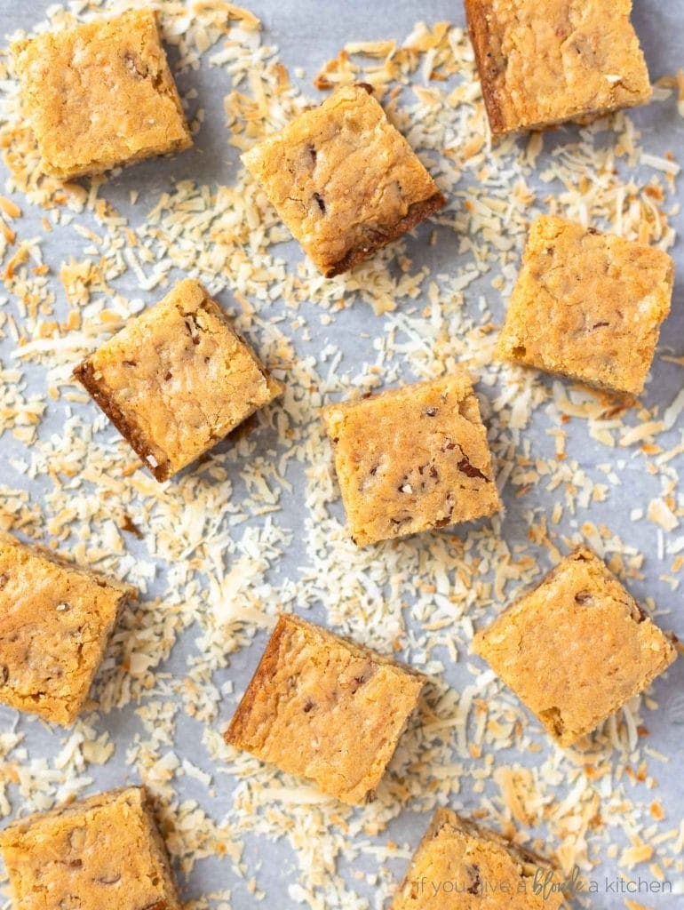 toasted coconut on cookie sheet with blondies on top cut into squares