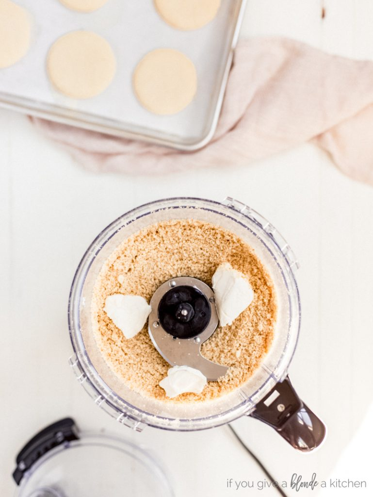 finely ground sugar cookie crumbs with dollops of cream cheese in food processor
