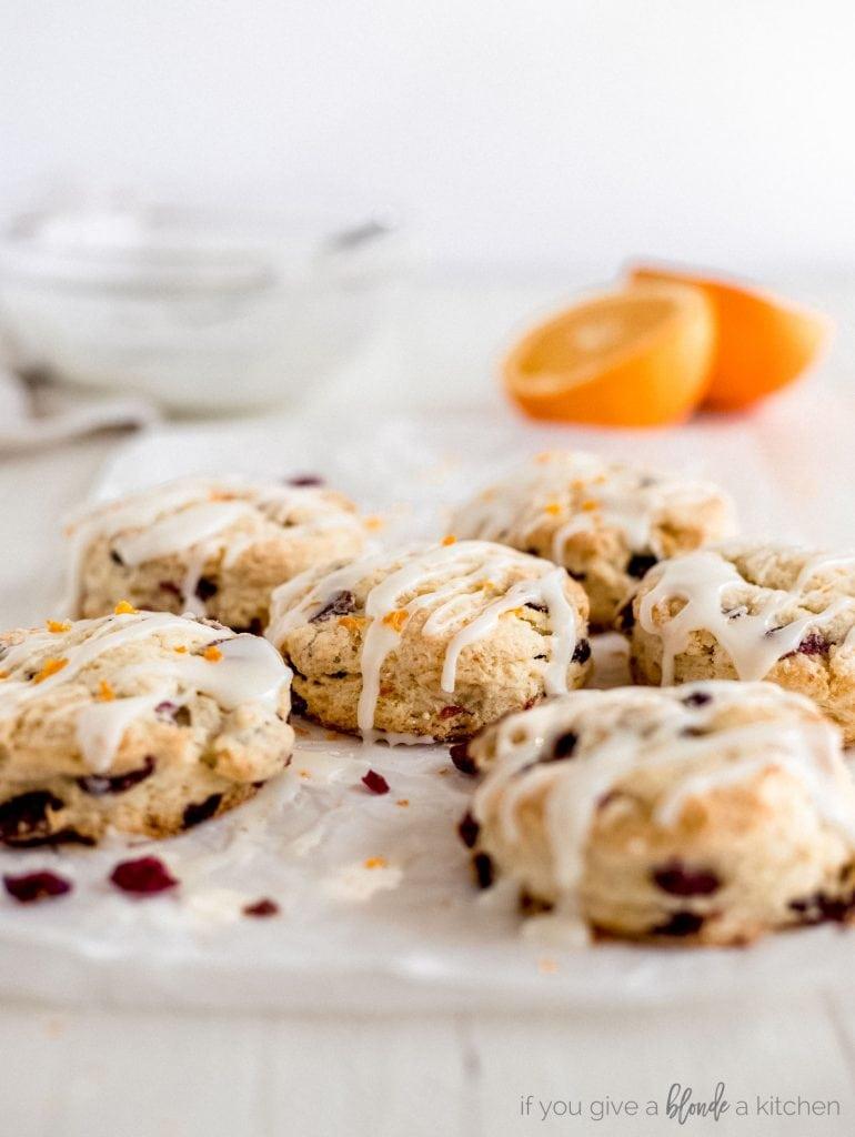 cranberry orange scones with glaze on parchment paper