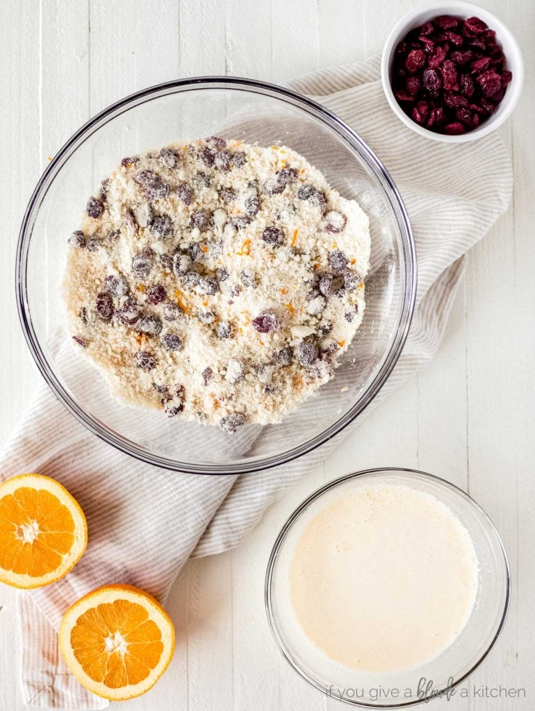 bowl of flour, cranberries, orange zest and butter, smaller bowl of cream