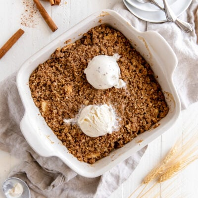 apple crisp in square ceramic baking dish with two scoops of vanilla ice cream on top