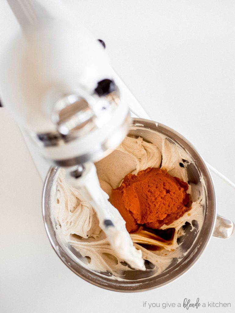 stand mixer with bowl of cheesecake batter and pumpkin puree