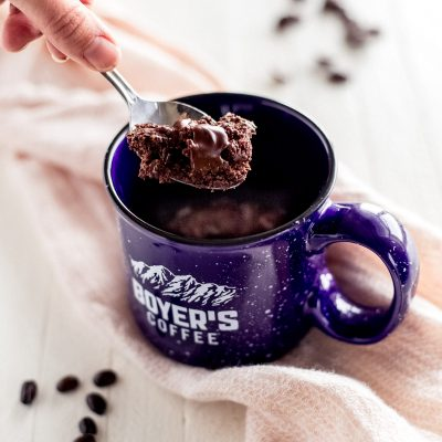 hand holding spoon with double chocolate chip cookie. Blue mug with cookie inside