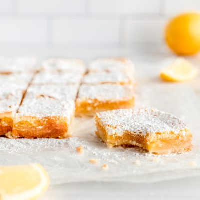 lemon bar square with bite and confectioners sugar on parchment paper