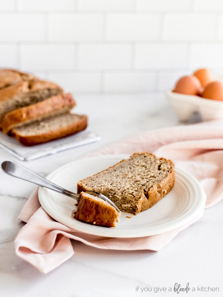 slice of banana bread on white plate with fork taking bite