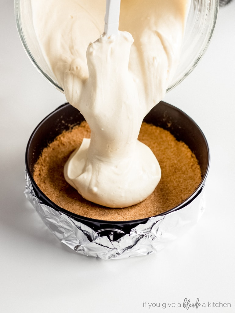 cheesecake batter poured into springform pan with graham cracker crust