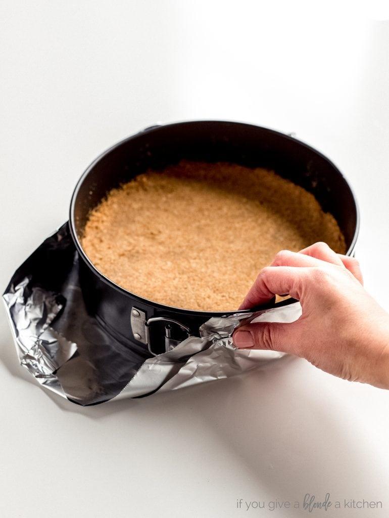 hand pressing aluminum foil up sides of springform pan