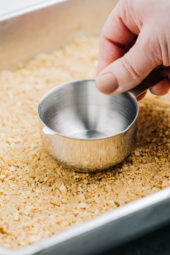 measuring cup press crushed graham crackers into baking pan