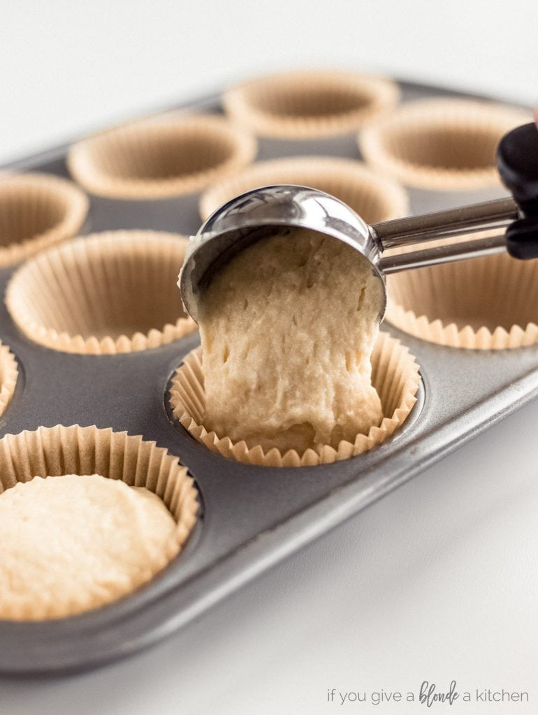 ice cream scoop transferring batter to paper lined muffin tin