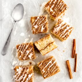 coffee cake square on parchment paper with vanilla glaze. Cinnamon stick and icing spoon