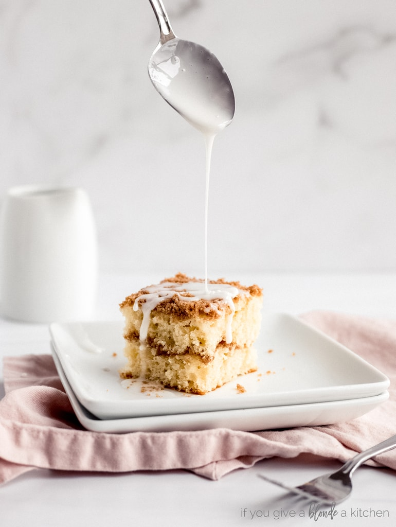 spoon drizzling icing over slice of coffee cake