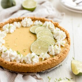graham cracker crust key lime pit with whipped cream florets and lime slices