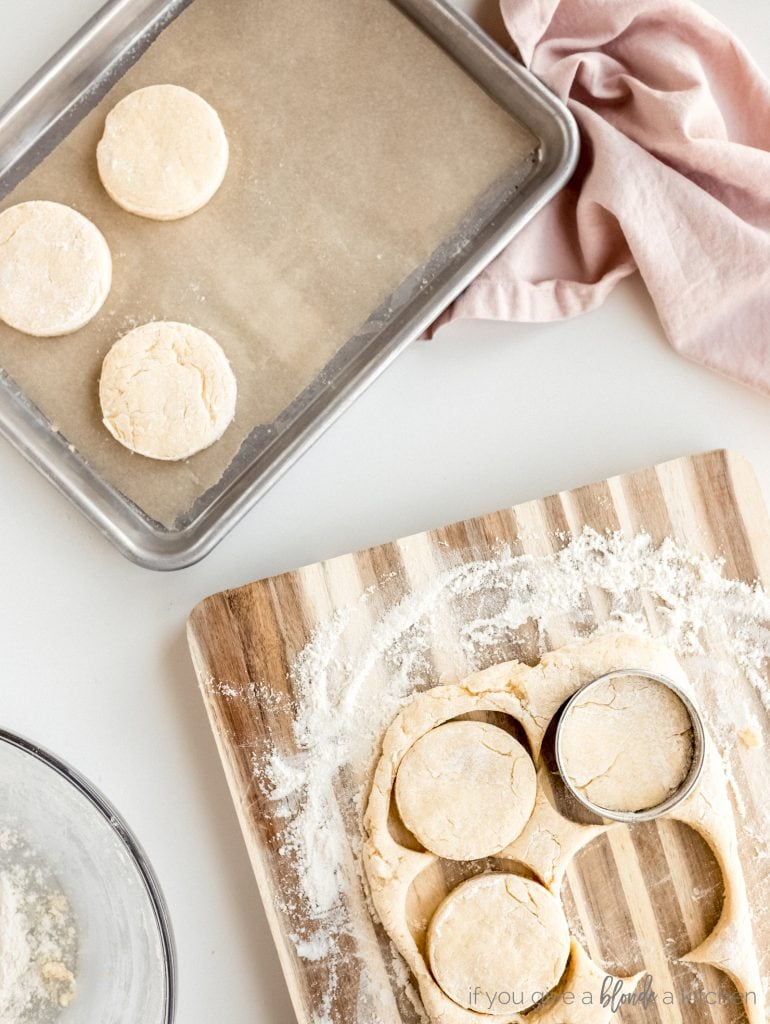 cutting board with flour and biscuit dough; baking sheet with biscuits