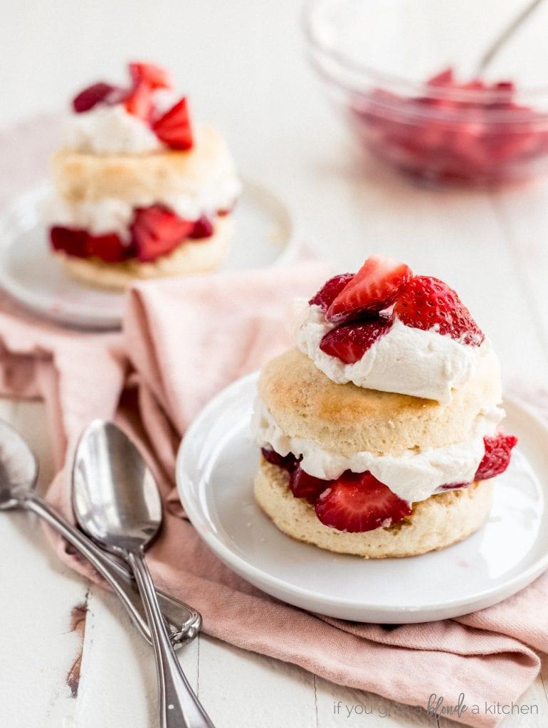 two strawberry shortcakes on white round plates