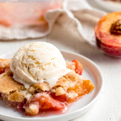 peach cobbler with scoop of melted vanilla ice cream on top