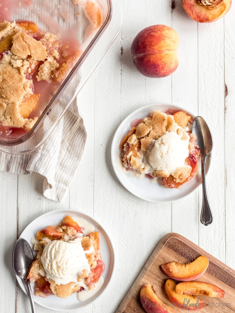 two round plates with peach cobbler and scoop of vanilla ice cream; small cutting board with peach slices; baking dish with peach cobbler