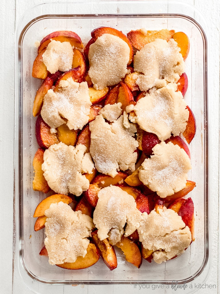 cinnamon sugar sprinkled on top of unbaked cobbler dough on top of peaches in glass baking pan