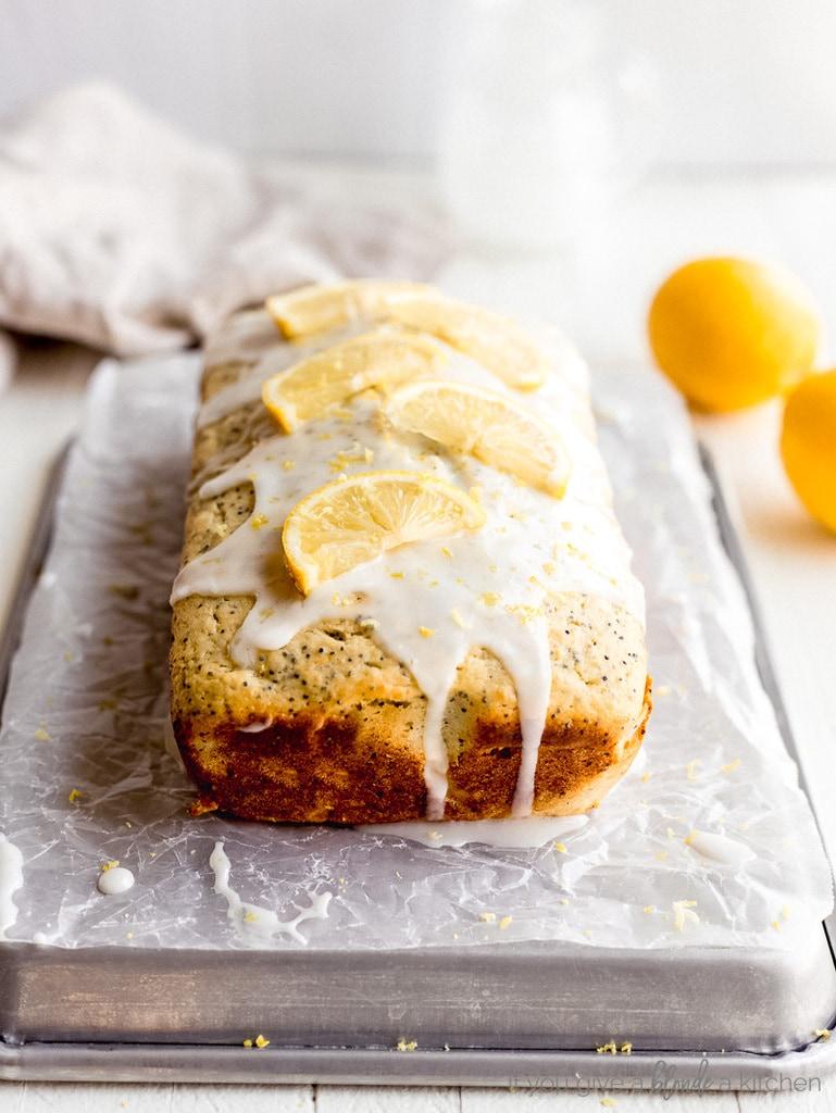 glaze dripping off loaf of lemon poppyseed bread. Lemon slice on top.
