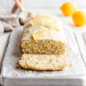 lemon poppyseed bread on parchment paper and baking sheet. end cut off showing inside of loaf.