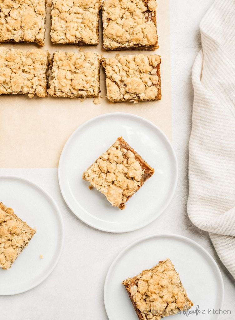 pumpkin pie bars cut into squares on parchment paper; three white plates with bars on each
