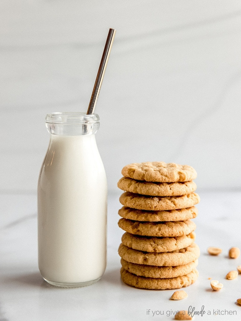 glass bottle of milk with metal straw next to stack of peanut butter cookies