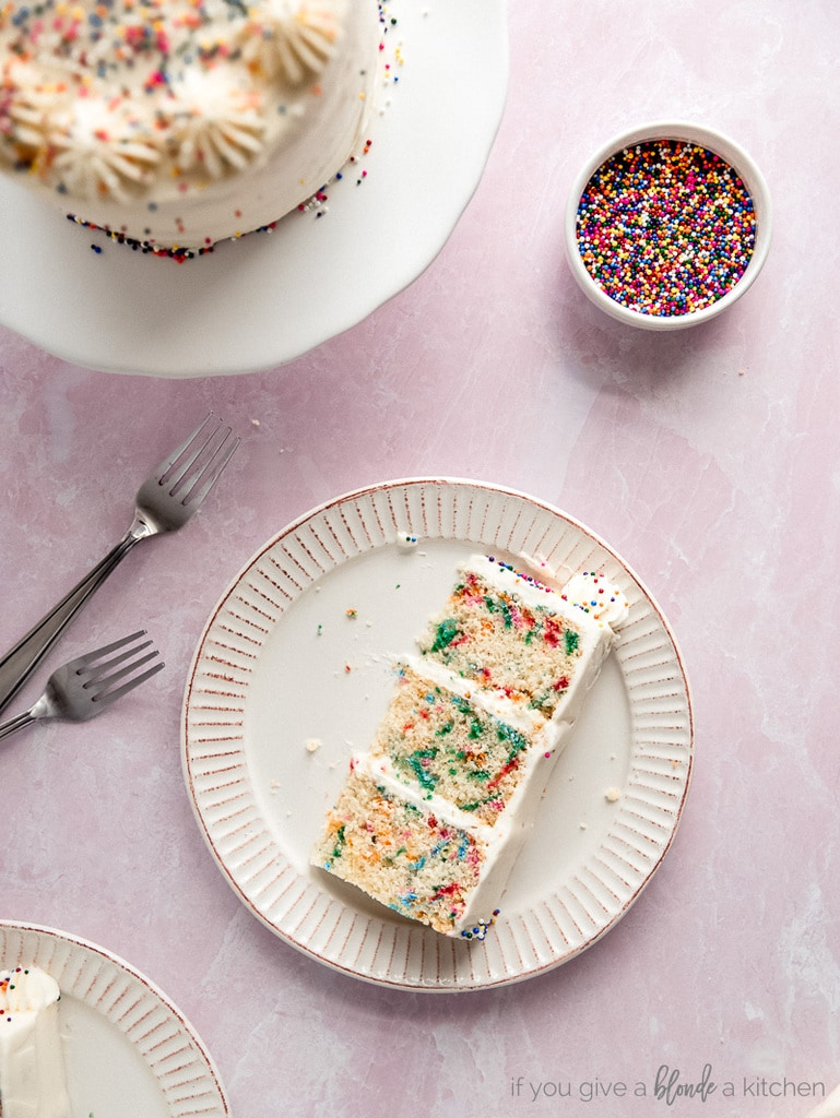 slice of layered funfetti cake on white plate; pink background and bowl of rainbow nonpareils