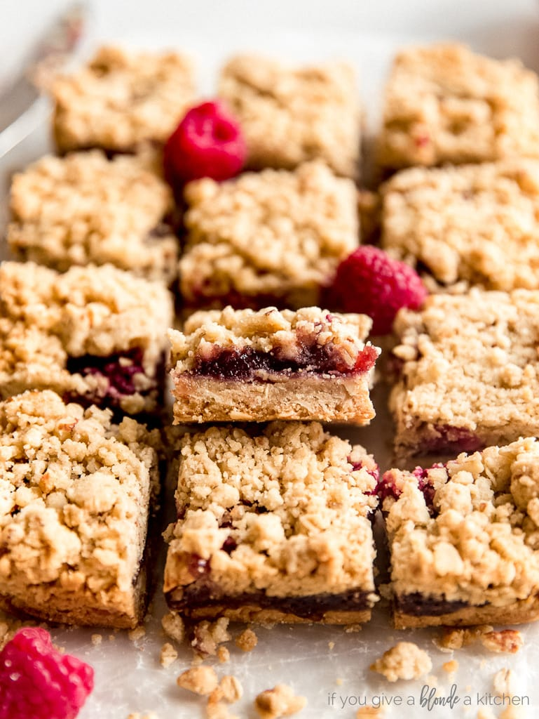 raspberry oatmeal bars with one propped up showing fruit filling