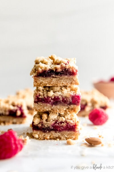 stack of three raspberry oatmeal bars with fresh raspberries next to it