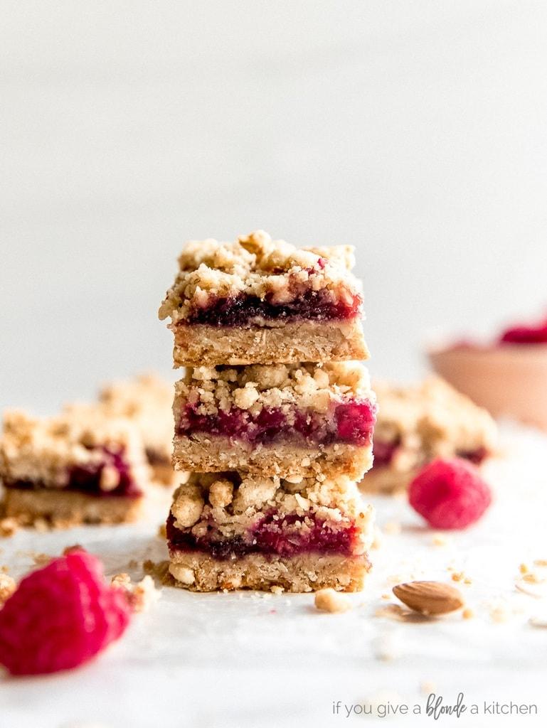 stack of three raspberry oatmeal bars with fresh raspberries next to it