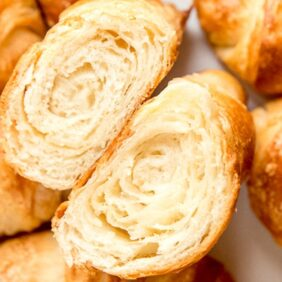 close up croissant cut in half showing layers. gold brown croissants next to cut croissant