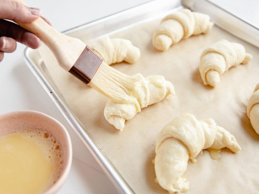 pastry brush adding egg wash to unbaked croissants on baking sheet