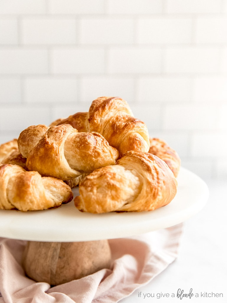 homemade croissants on bake stand; subway tile in the background
