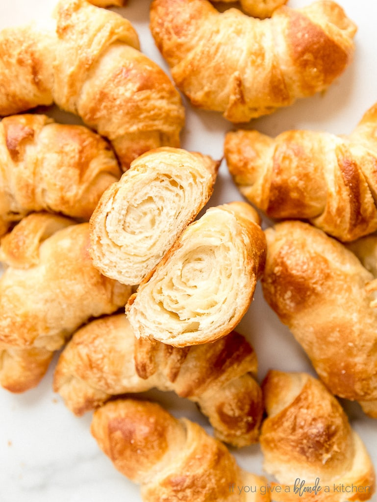 croissants on white surface and one croissant cut open showing layers inside