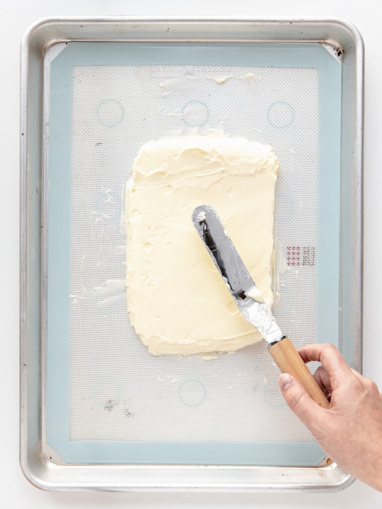 offset spatula spreading butter into a rectangle on silpat